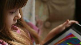 Маленькая девочка рисует на таблетке акции видеоматериалы
