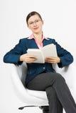 Маленькая девочка сидит в белом стуле с книгой Стоковая Фотография