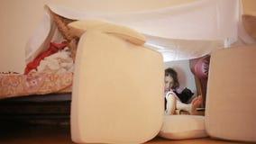 Маленькая девочка сидит в временном доме подушек и дома одеяла сток-видео