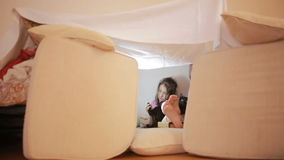 Маленькая девочка сидит в временном доме подушек и дома одеяла акции видеоматериалы