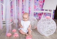 Маленькая девочка сидит на поле в питомнике стоковые фотографии rf