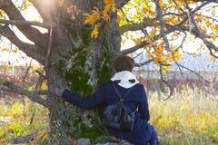 Маленькая девочка сидит под деревом Стоковые Фотографии RF