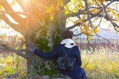 Маленькая девочка сидит под деревом Стоковое Изображение