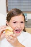 Маленькая девочка сидя в дантистах предводительствует держать модельные зубы Стоковые Фото