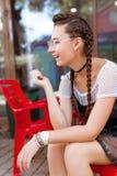 Маленькая девочка сидя в кафе и усмехаться стоковое фото