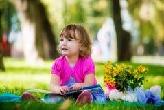 Маленькая девочка сидя в парке и читая книгу Стоковое фото RF