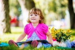 Маленькая девочка сидя в парке и читая книгу Стоковые Изображения
