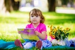 Маленькая девочка сидя в парке и читая книгу Стоковое Фото