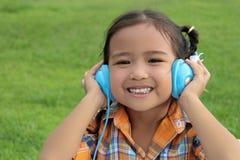 Маленькая девочка сидя в парке Стоковые Изображения
