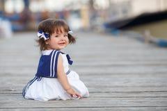 Маленькая девочка сидя на деревянной пристани Стоковые Фото