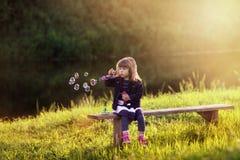 Маленькая девочка сидя на деревянной скамье дует пузыри в лучах Стоковая Фотография RF
