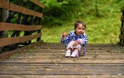 Маленькая девочка сидя на мосте Стоковые Изображения RF
