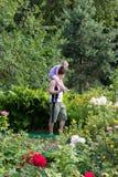 Маленькая девочка сидя на папе взваливает на плечи среди цветков Стоковое фото RF