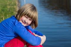Маленькая девочка сидя на портовом районе стоковое изображение rf