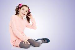 Маленькая девочка сидя на поле и выправляет волосы Стоковые Фотографии RF