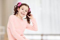 Маленькая девочка сидя на поле и выправляет волосы Стоковое Фото