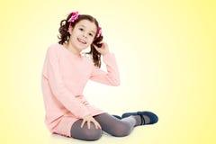 Маленькая девочка сидя на поле и выправляет волосы Стоковая Фотография