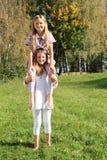 Маленькая девочка сидя на плечах girlsСтоковое фото RF
