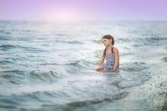 Маленькая девочка сидя на пляже Стоковое фото RF