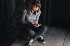 Маленькая девочка сидя на скейтборде с наушниками и таблеткой Стоковые Фотографии RF