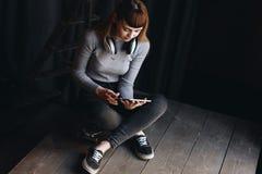 Маленькая девочка сидя на скейтборде с наушниками и таблеткой Стоковые Изображения