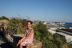 Маленькая девочка сидя на стене обозревая Pozzuoli Стоковые Фотографии RF