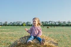 Маленькая девочка сидя на стоге сена Стоковое Фото
