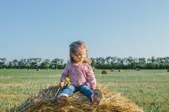 Маленькая девочка сидя на стоге сена Стоковые Изображения RF
