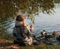 Маленькая девочка сидя на стороне озера, смотрящ уток воды и подавать Стоковые Изображения RF