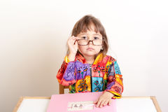 Маленькая девочка сидя на столе и рассматривая ее стекла Стоковая Фотография