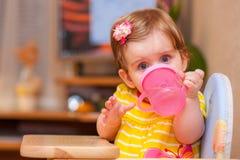Маленькая девочка сидя на таблице Вода питья Стоковые Изображения