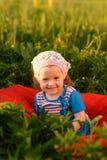 Маленькая девочка сидя на траве Стоковое Фото