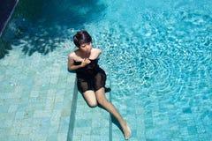 Маленькая девочка сидя на шагах бассейна в a стоковые фотографии rf
