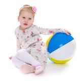 Маленькая девочка сидя на шарике пола и игры стоковые изображения