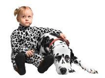 Маленькая девочка сидя около далматинской собаки Стоковые Фотографии RF