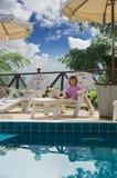 Маленькая девочка сидя около бассейна Стоковое фото RF
