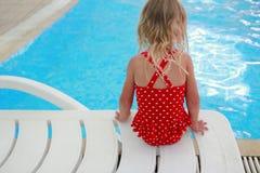 Маленькая девочка сидя около бассейна Стоковые Изображения RF