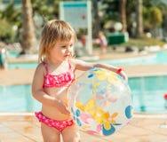 Маленькая девочка сидя около бассейна Стоковая Фотография RF