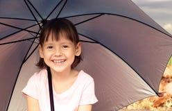 Маленькая девочка сидя под зонтиком Стоковые Фотографии RF