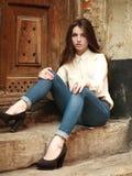 Маленькая девочка сидя outdoors унылое, на предпосылке старый дом стоковая фотография rf