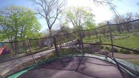 Маленькая девочка скача на батут движение медленное сток-видео