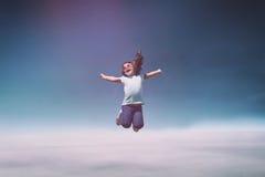 Маленькая девочка скача на голубое небо стоковые фото