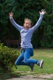 Маленькая девочка скача для того чтобы выразить утеху Стоковое Фото