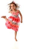 Маленькая девочка скачет в воздух, празднуя был активна Стоковое фото RF