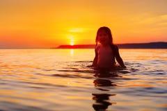 Маленькая девочка смеясь над и плача в брызге волн на море Стоковое Фото