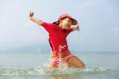 Маленькая девочка смеясь над и плача в брызге волн на море Стоковое фото RF
