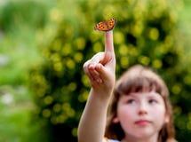 Маленькая девочка смотрит бабочку Urticae l Aglais Стоковое Изображение