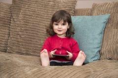 Маленькая девочка смотрит вверх от таблетки Стоковые Изображения RF