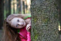 Маленькая девочка смотрит от за дерева в лесе Стоковое Фото