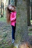 Маленькая девочка смотрит от за дерева в лесе Стоковые Фотографии RF